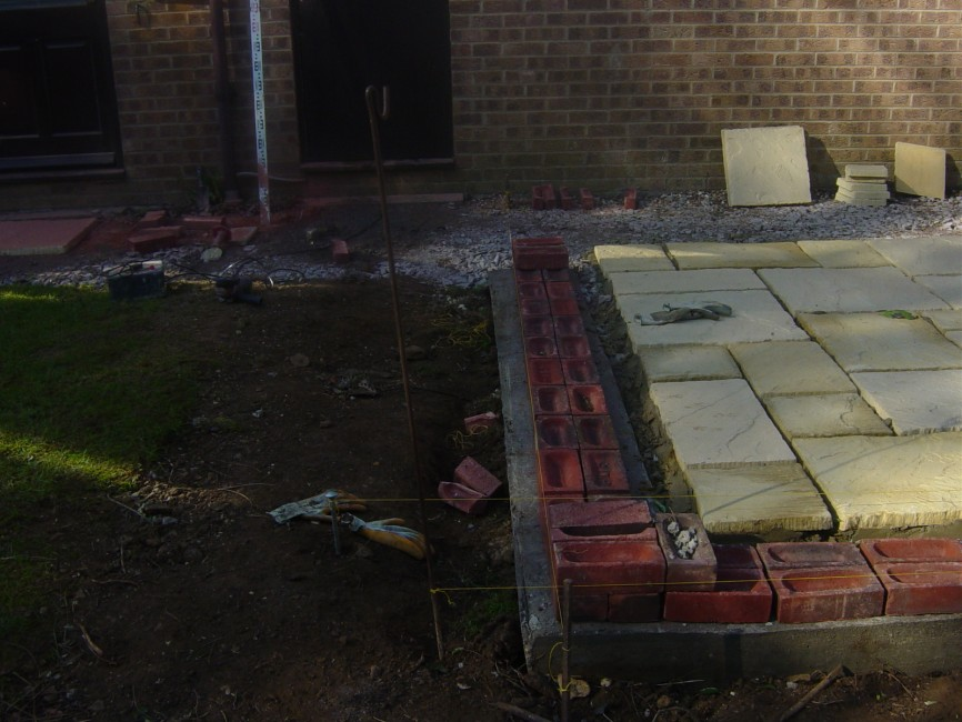 York stone patio and wall landscaped garden by Indigo Landscapers in Northamptonshire
